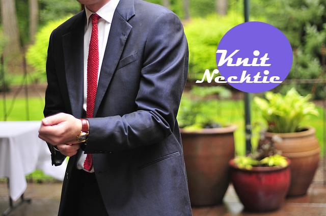 Mann in dunklem Anzug mit roter, gestrickter Krawatte
