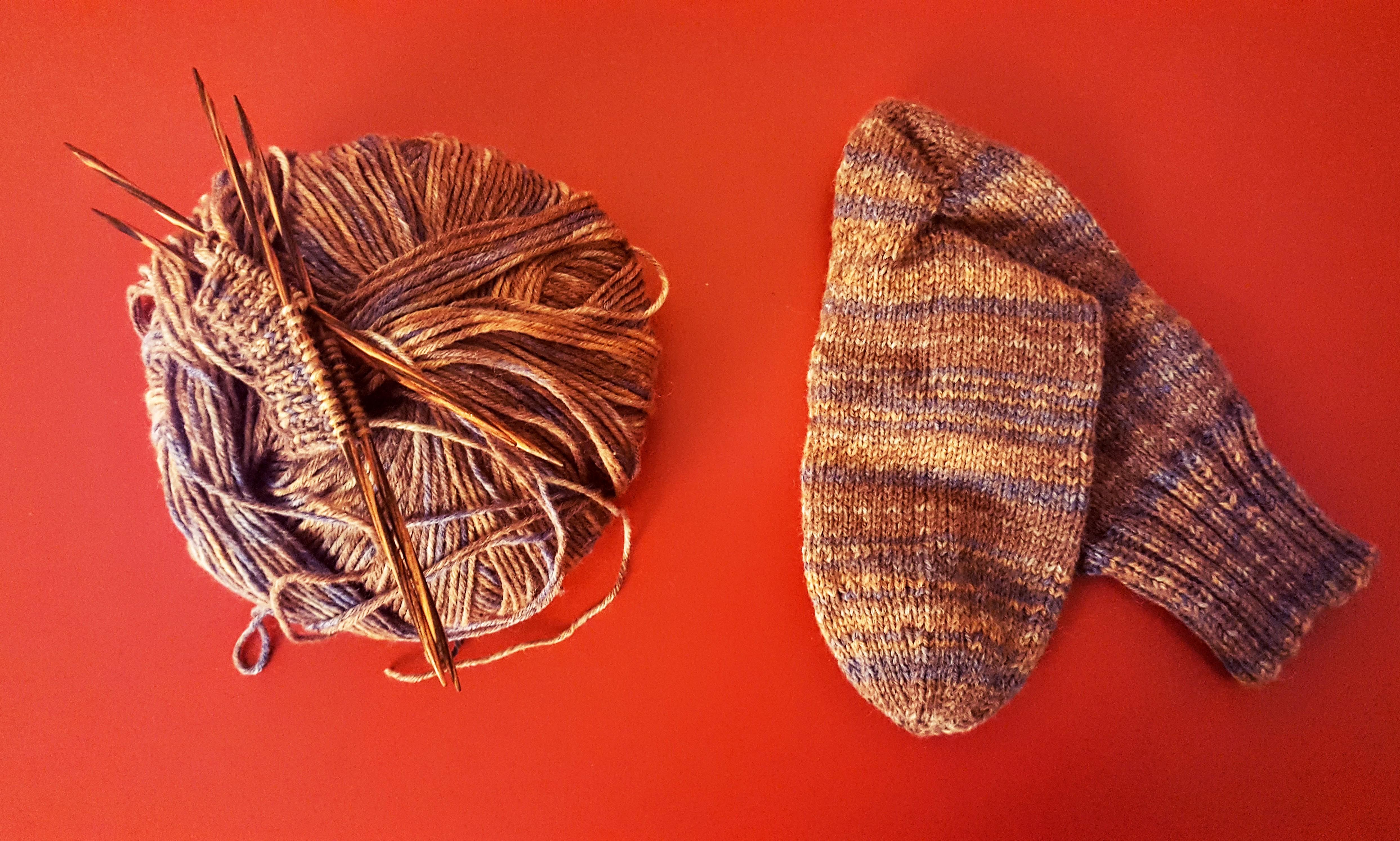Ein Knäul Austermann Wolle liegt links von einem fertig gestrickten Socken