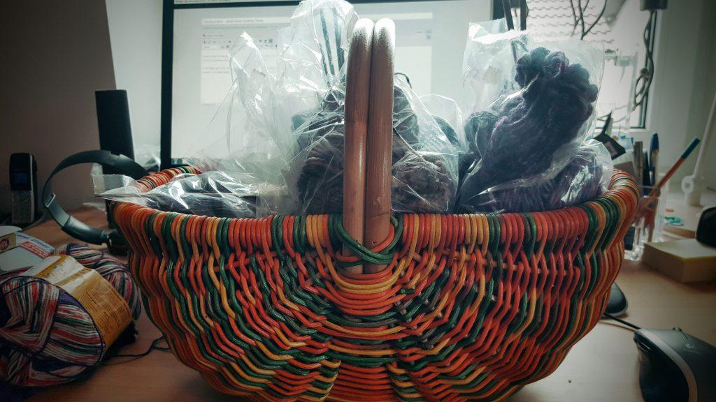 Ein bunter Weidenkorb voller unfertig gestrickter Socken