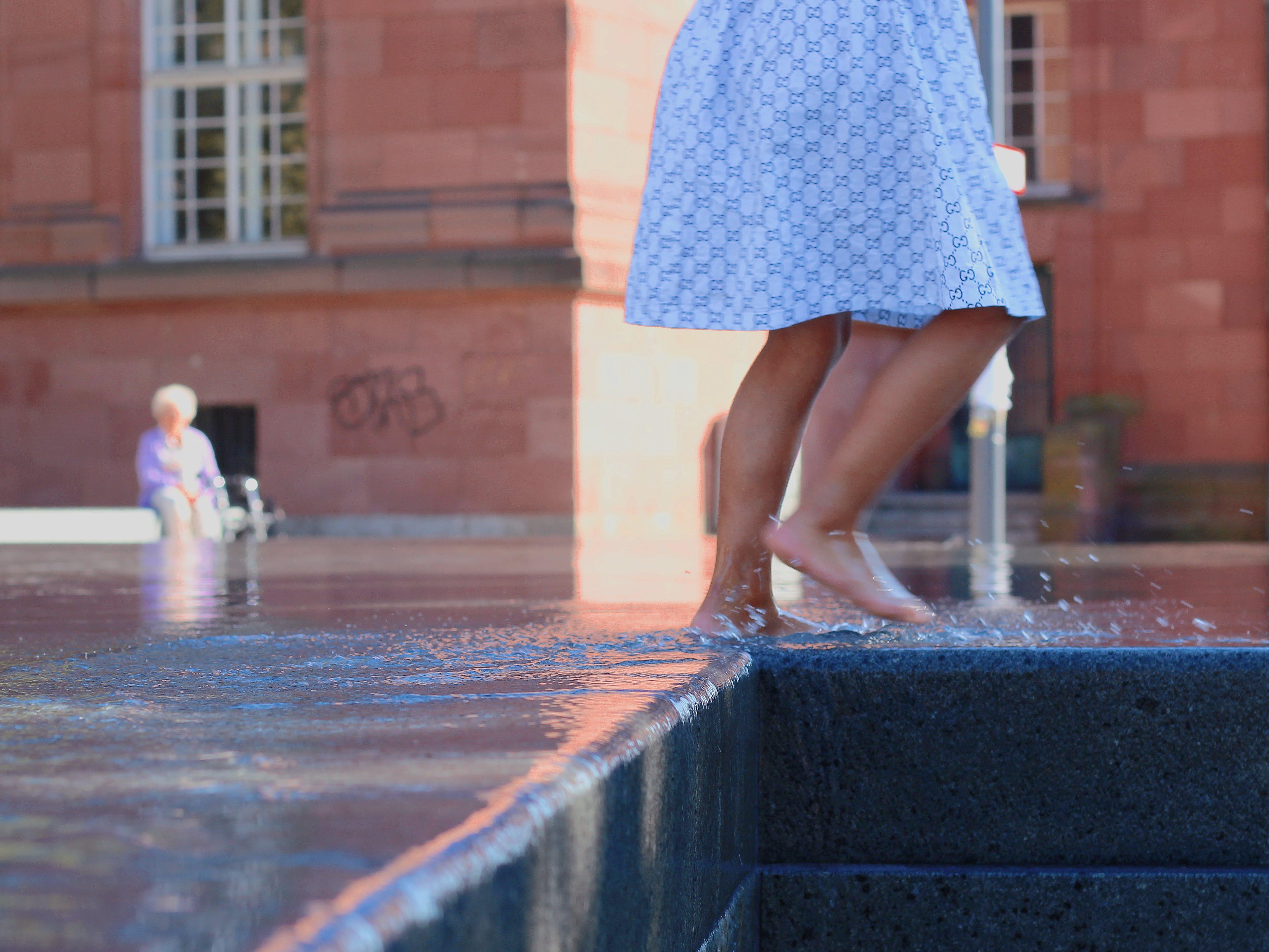 Ein Mädchen läuft auf dem Denkmal der Freiburger Synagoge