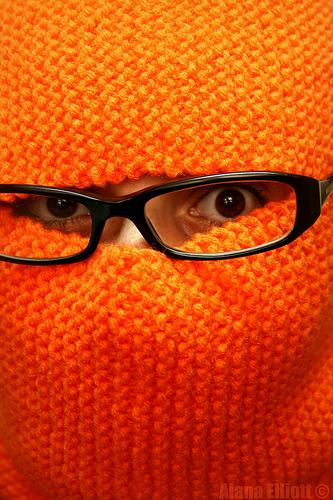 Orangene gestrickte Haube zu sehen ist nur ein AUgenpaar und eine schwarze Brille