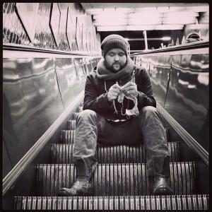 Mann mit Bart sitzt auf einer Rolltreppe und strickt