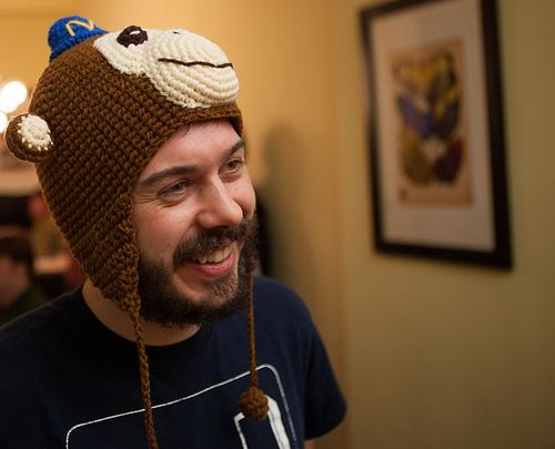 Mann mit Bart und einer Mütze auf dem Kopf die aussieht wie ein Affe