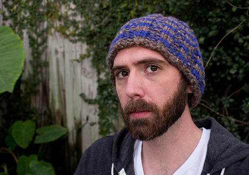 Ein Mann mit Bart mit einer gestrickten Mütze auf dem Kopf