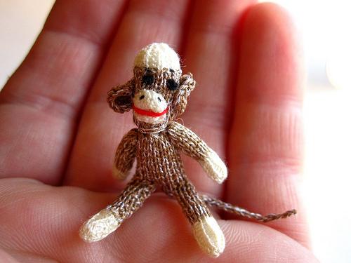 Sehr kleiner, gestrickter Affe in der Mitte einer Hand