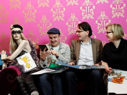 drei Moderatoren sitzen neben einer Schaufensterpuppe auf einer Couch