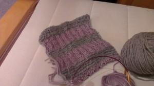 Der Anfang eines Schals in blass lila und grauen Streifen