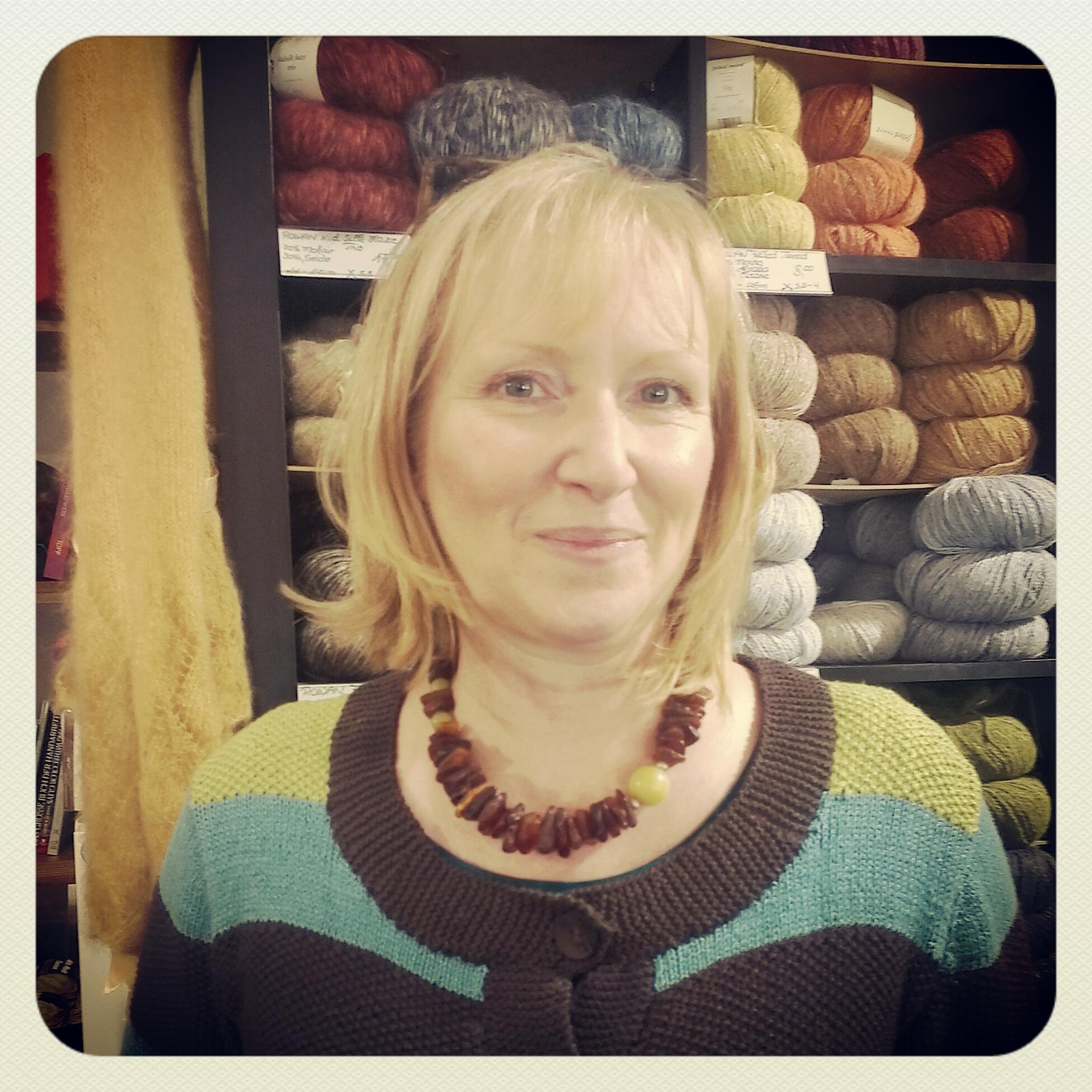 Blonde Frau mit mittellangen Haaren steht vor einem Regal mit einer großen Auswahl an Wollknäulen