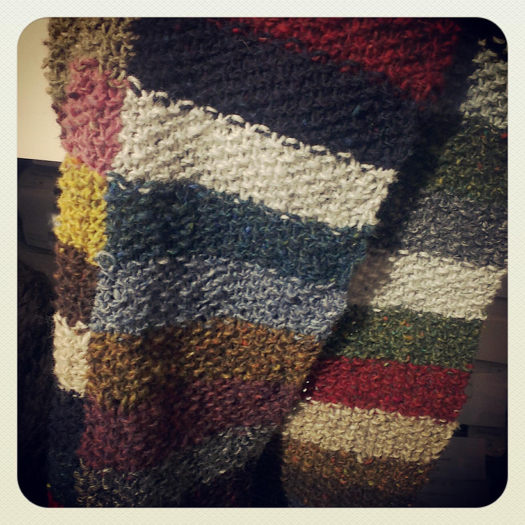 Eine gestrickte Decke mit vielen verschiedenen Farben