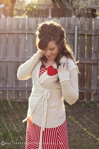 Frau steht im Garten und trägt auf ihrer weißen Strickjacke ein gestricktes Herz